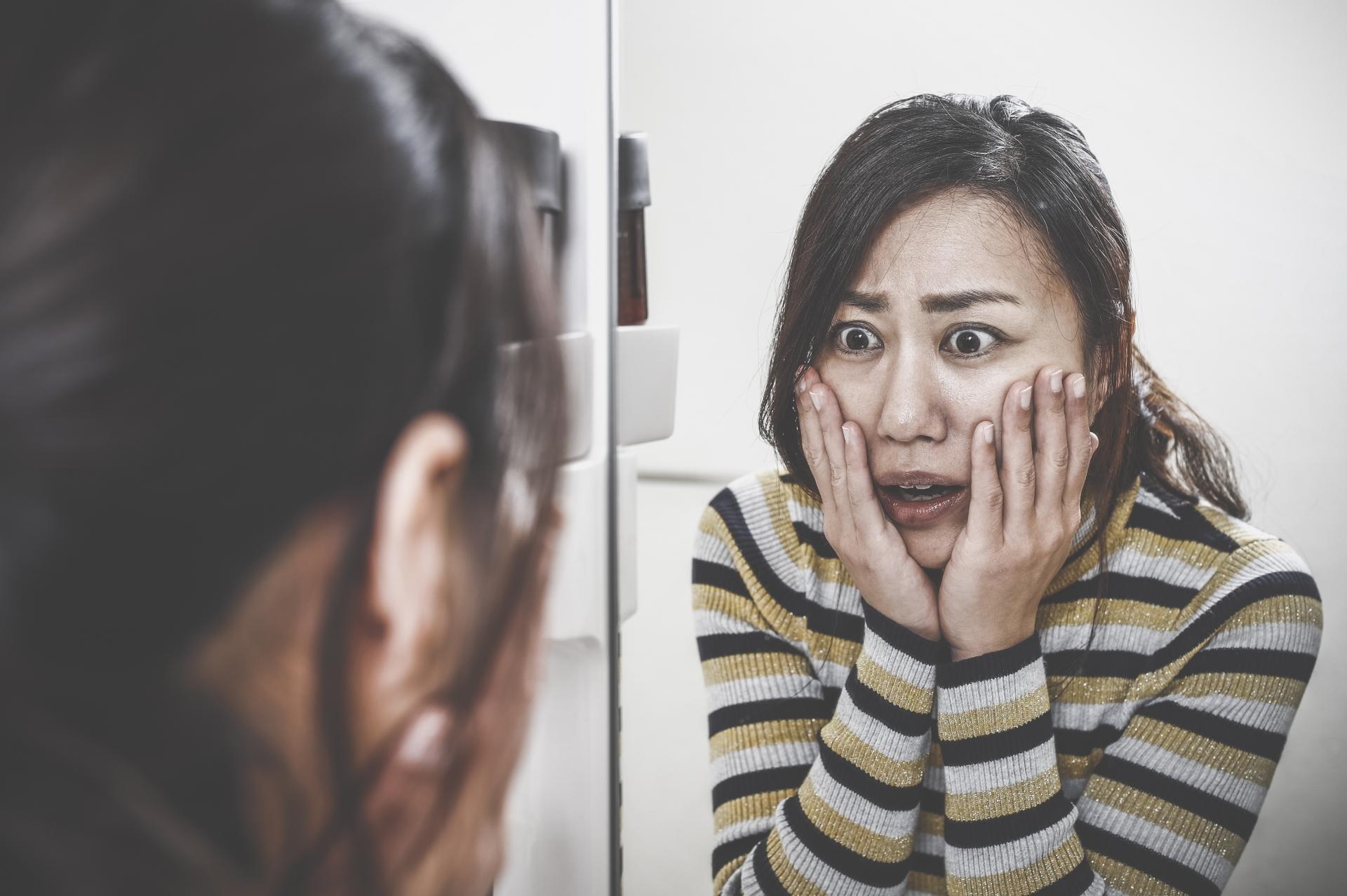鏡を見てショックを受ける女性